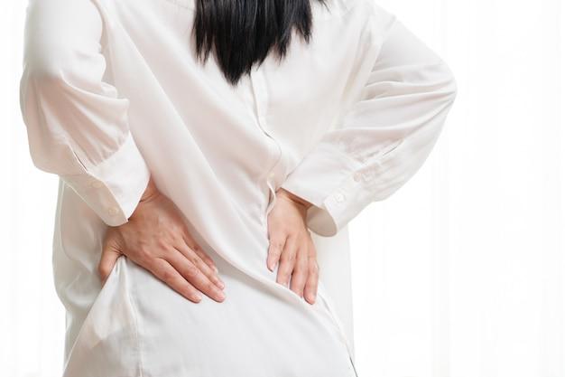 Ból pleców w domu. kobiety cierpią na bóle pleców.