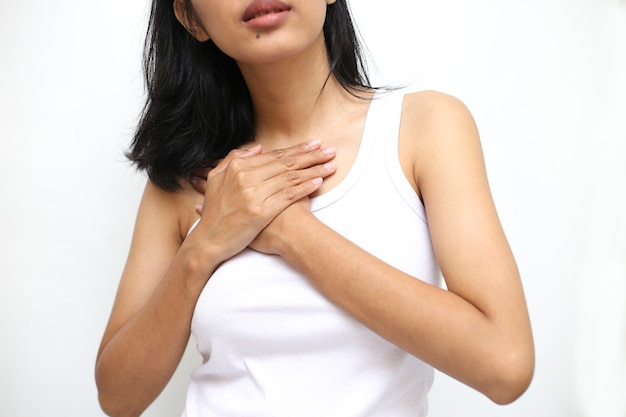Ból serca. piękna azjatycka kobieta cierpi na ból w klatce piersiowej