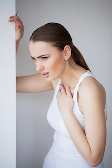 Ból serca. piękna kobieta cierpi na ból w klatce piersiowej. problemy zdrowotne