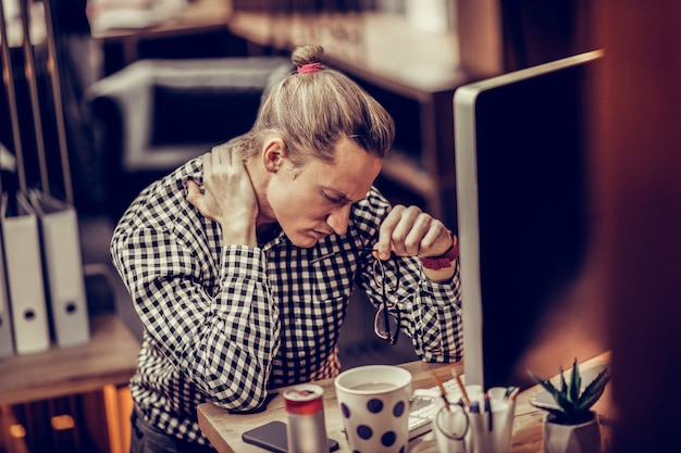 Ból szyi. negatywny zachwycony mężczyzna pochylający głowę i dotykający jego szyi