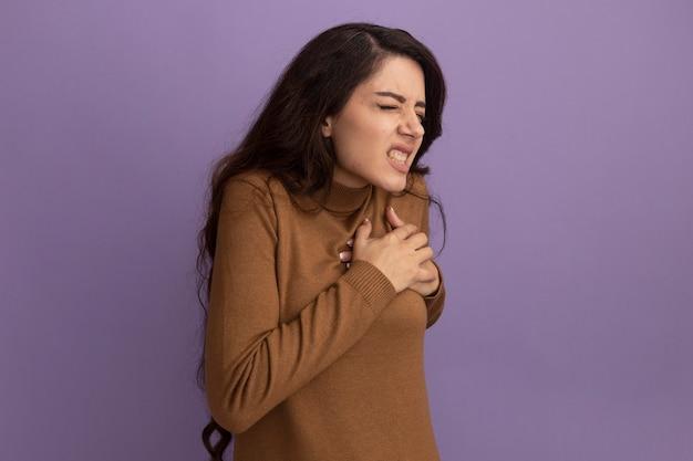 Ból z zamkniętymi oczami młoda piękna dziewczyna w brązowym swetrze z golfem, kładąca rękę na sercu na fioletowej ścianie z kopią miejsca