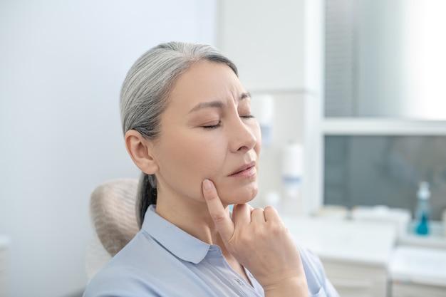 Ból zęba. dojrzała kaukaska kobieta cierpi na ból zęba