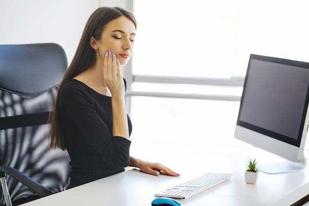 Ból zęba. pojęcie zdrowia jamy ustnej. portret młodej kobiety smutne, mając ból zęba, siedząc w swoim biurze.