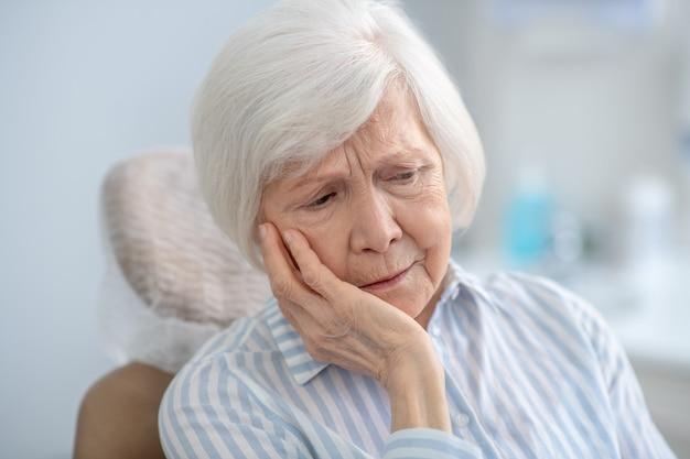 Ból zęba. zbliżenie na siwowłosą kobietę cierpiącą na ból zęba