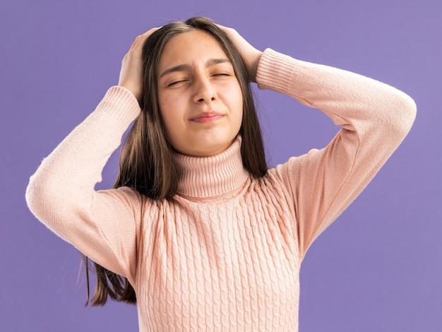 Boląca ładna nastolatka trzymająca ręce na głowie z zamkniętymi oczami na fioletowej ścianie