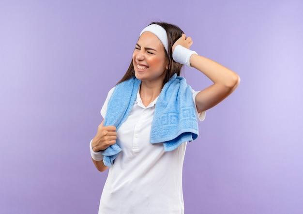 Boląca ładna wysportowana dziewczyna nosząca opaskę na głowę i nadgarstek, kładąc rękę na głowie, zamykając oczy ręcznikiem wokół szyi na fioletowej ścianie