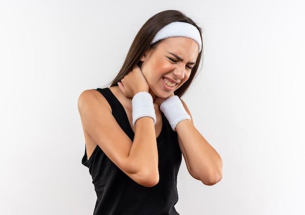 Boląca ładna wysportowana dziewczyna nosząca opaskę na głowę i nadgarstek kładąca ręce na szyi z zamkniętymi oczami na białej ścianie
