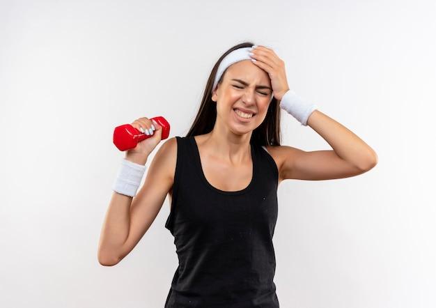 Boląca ładna wysportowana dziewczyna nosząca opaskę na głowę i nadgarstek trzymająca hantle cierpiąca na ból głowy z ręką na głowie i zamkniętymi oczami na białym tle na białej ścianie