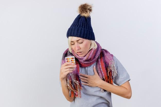 Boląca młoda blondynka chora słowiańska kobieta w czapce zimowej i szaliku kładzie rękę na klatce piersiowej i trzyma paczkę tabletek medycznych na białej ścianie z miejscem na kopię