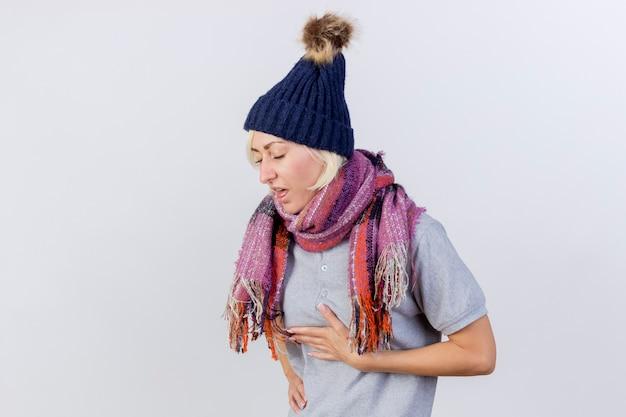 Boląca młoda blondynka chora słowiańska kobieta w czapce zimowej i szaliku kładzie rękę na klatce piersiowej na białym tle na białej ścianie z miejsca na kopię