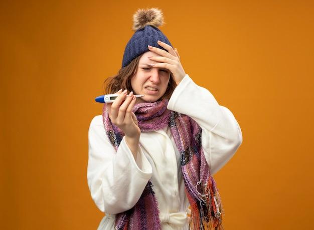 Boląca młoda chora dziewczyna ubrana w białą szatę i czapkę zimową z szalikiem trzymając termometr kładąc rękę na świątyni na białym tle na pomarańczowo