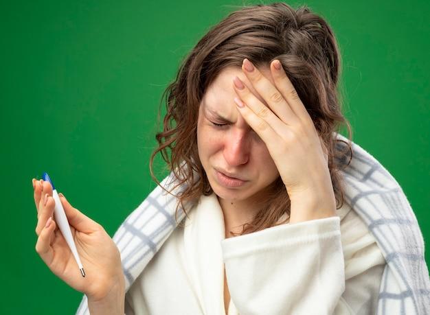 Boląca młoda chora dziewczyna ubrana w białą szatę owiniętą w kratę trzymająca termometr trzymająca termometr kładąca dłoń na czole odizolowana na zielono