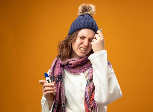 Boląca młoda chora dziewczyna w białej szacie i czapce zimowej z szalikiem trzymająca termometr z pigułkami kładąca dłoń na czole odizolowana na pomarańczowej ścianie