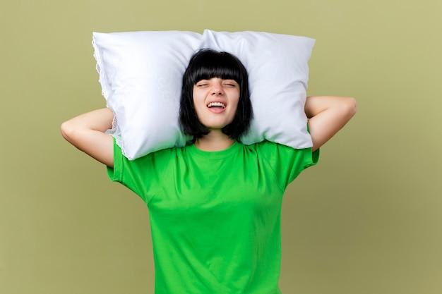 Boląca młoda chora dziewczynka kaukaski trzymając poduszkę pod głową z zamkniętymi oczami na białym tle na oliwkowym tle