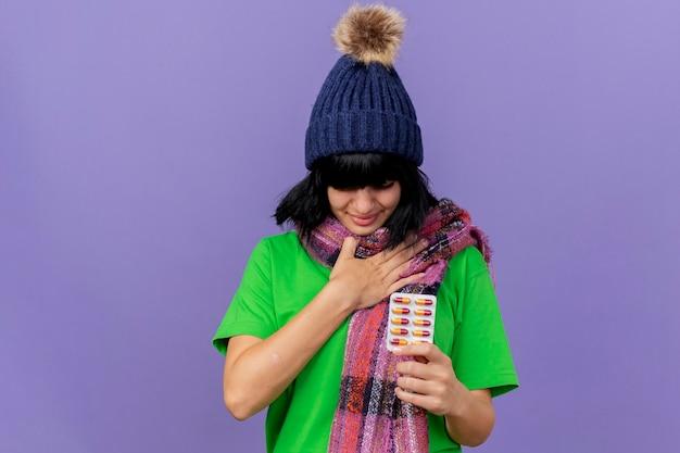 Boląca młoda chora kobieta w czapce zimowej i szaliku trzymająca paczkę kapsułek trzymając rękę na klatce piersiowej z zamkniętymi oczami odizolowanymi na fioletowej ścianie