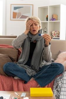 Boląca młoda, chora słowiańska kobieta z szalikiem na szyi kładzie rękę na czole trzymając i patrząc na termometr siedząc na kanapie w salonie