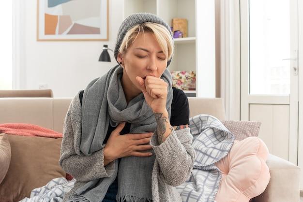 Boląca młoda, chora słowiańska kobieta z szalikiem na szyi w czapce zimowej, kaszląca, trzymająca pięść przy ustach, siedząca na kanapie w salonie