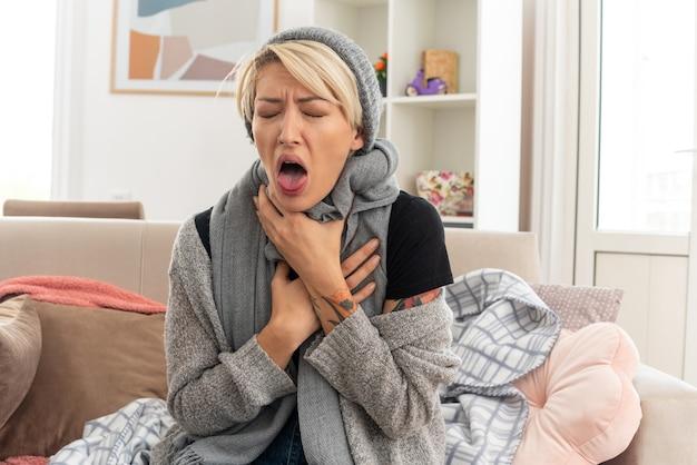 Boląca młoda, chora słowiańska kobieta z szalikiem na szyi w czapce zimowej trzymająca się za szyję, siedząca na kanapie w salonie
