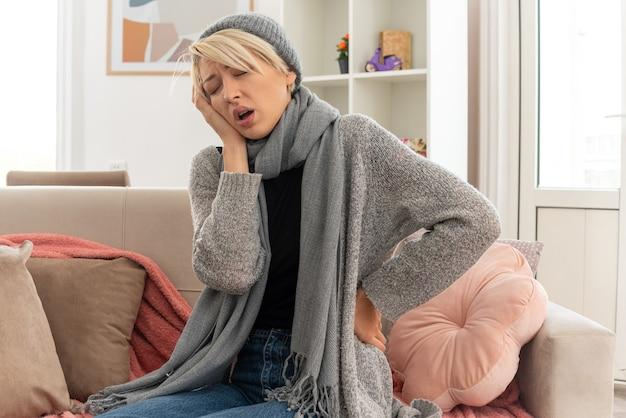 Boląca młoda, chora słowiańska kobieta z szalikiem na szyi w zimowym kapeluszu, kładąca dłoń na twarzy, siedząca na kanapie w salonie