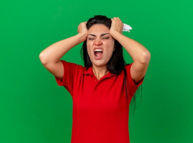 Boląca młoda kaukaski chora dziewczyna kładzie ręce na głowę z zamkniętymi oczami cierpi na bóle głowy z serwetką w ręku na białym tle na zielonej ścianie
