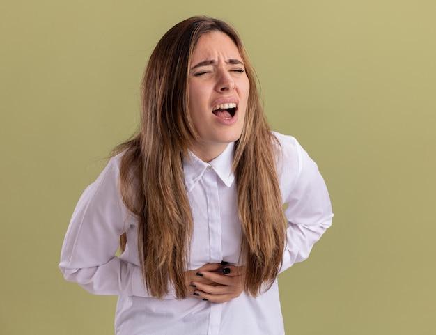 Boląca młoda ładna dziewczyna kaukaski kładzie ręce na brzuchu odizolowane na oliwkowej ścianie z miejsca na kopię