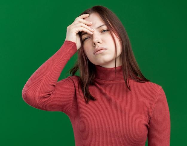 Boląca młoda ładna dziewczyna patrząca na bok trzymając rękę na głowie odizolowaną na zielonej ścianie