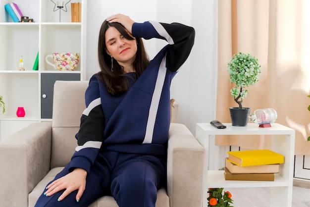 Boląca młoda ładna kaukaska kobieta siedząca na fotelu w zaprojektowanym salonie kładąca dłoń na nodze, a druga na głowie cierpiąca na ból głowy z zamkniętymi oczami