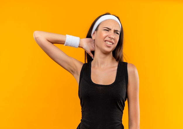 Boląca młoda, ładna sportowa dziewczyna nosząca opaskę na głowę i nadgarstek, kładąc rękę na szyi, patrząc na bok na pomarańczowej ścianie