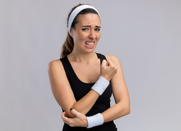 Boląca młoda, ładna sportowa kobieta nosząca opaskę i opaski dotykające łokcia