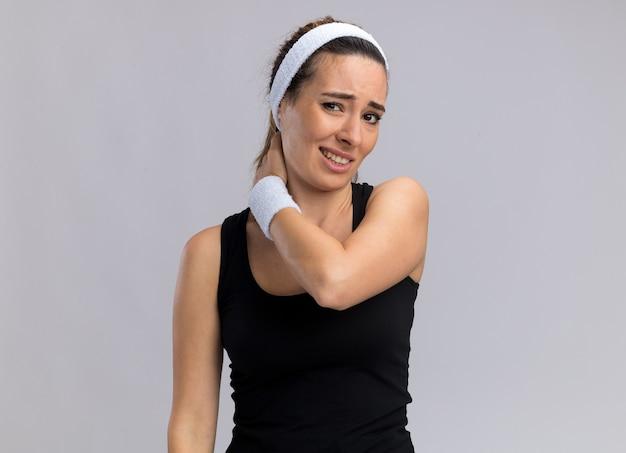 Boląca młoda ładna sportowa kobieta nosząca opaskę i opaski, patrząc na przód, kładąc rękę na szyi na białym tle na białej ścianie z kopią przestrzeni