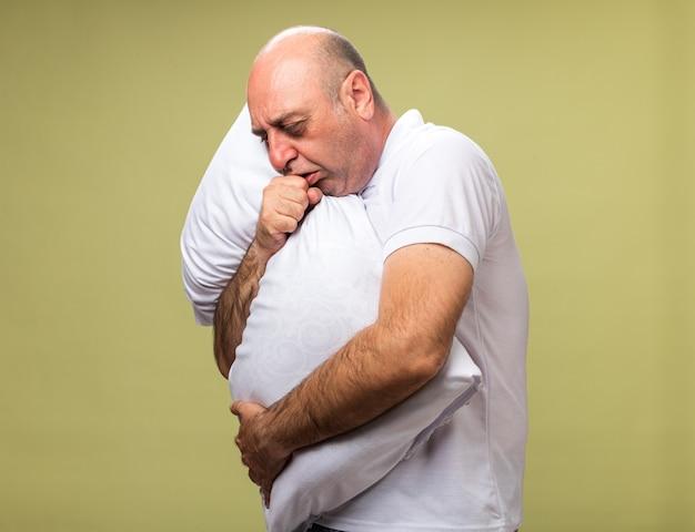 Bolący dorosły chory kaukaski mężczyzna kaszle, trzymając poduszkę na białym tle na oliwkowej ścianie z miejsca na kopię