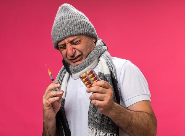 Bolący dorosły chory kaukaski mężczyzna z szalikiem na szyi w czapce zimowej trzymający strzykawkę i blister z lekami odizolowany na różowej ścianie z miejscem na kopię