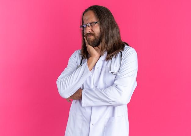 Bolący dorosły lekarz mężczyzna ubrany w szatę medyczną i stetoskop w okularach trzymający rękę na policzku cierpiący na ból zęba z zamkniętymi oczami