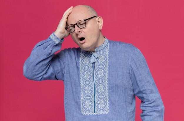 Bolący dorosły słowiański mężczyzna w niebieskiej koszuli w okularach optycznych, kładąc rękę na głowie