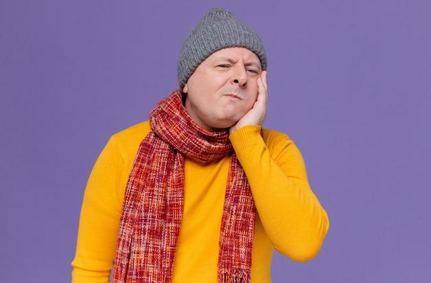 Bolący dorosły słowiański mężczyzna w zimowej czapce i szaliku na szyi, kładący dłoń na twarzy