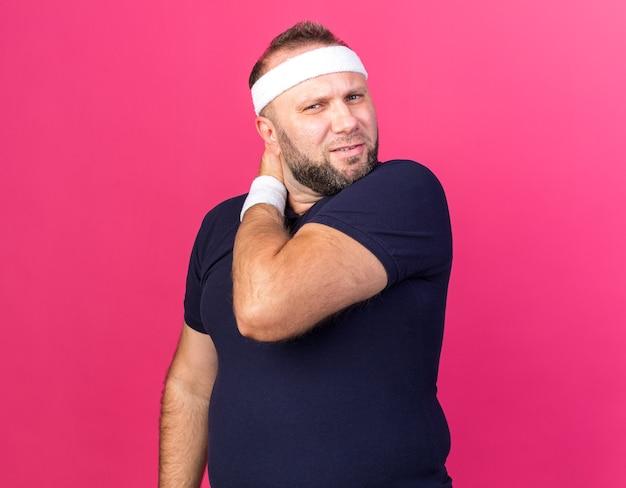 Bolący dorosły słowiański sportowy mężczyzna noszący opaskę i opaski na nadgarstek, kładąc dłoń na szyi na białym tle na różowej ścianie z miejsca na kopię