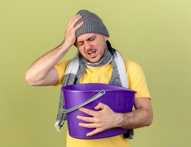Bolący młody blond chory słowiański mężczyzna w czapce zimowej i szaliku kładzie rękę na głowie i trzyma plastikowe wiadro odizolowane na oliwkowej ścianie z miejscem na kopię