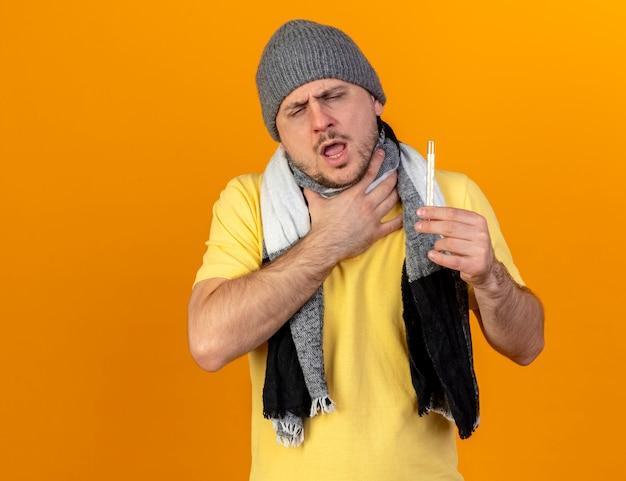 Bolący młody blondyn chory słowiański w czapce zimowej i szaliku kładzie rękę na szyi