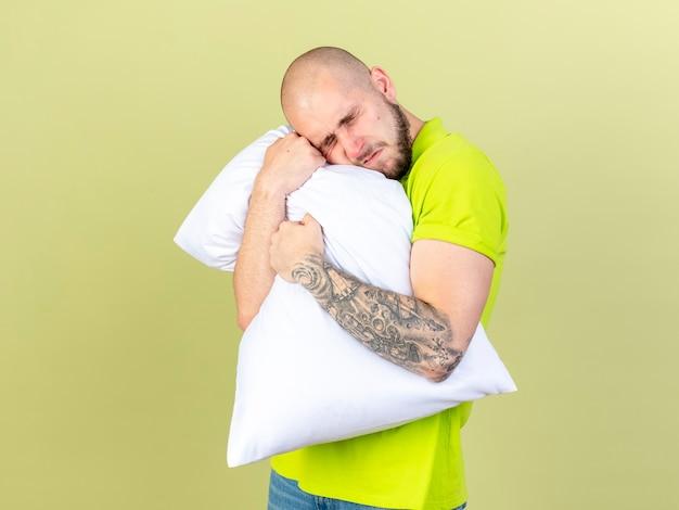 Bolący młody chory człowiek trzyma i kładzie głowę na poduszce na białym tle na oliwkowej ścianie