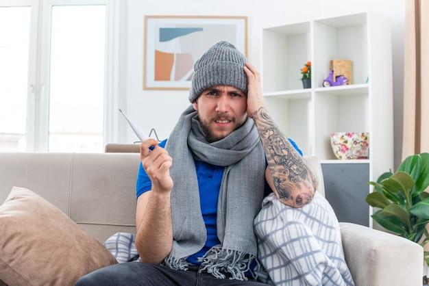 Bolący młody chory mężczyzna ubrany w szalik i czapkę zimową, siedzący na kanapie w salonie, trzymający termometr trzymający rękę na głowie