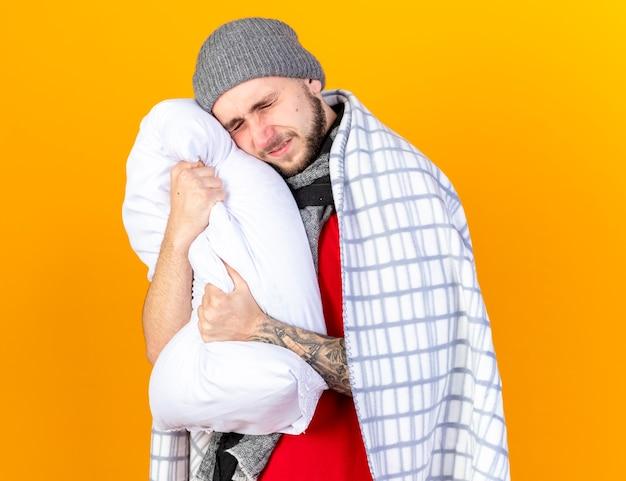 Bolący młody chory mężczyzna w czapce zimowej i szaliku przytula i kładzie głowę na poduszce owiniętej w kratę odizolowaną na pomarańczowej ścianie