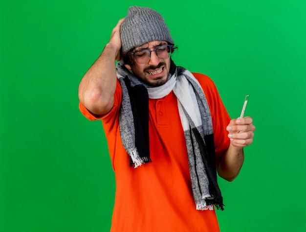 Bolący młody chory mężczyzna w okularach czapka zimowa i szalik trzymający termometr trzymający rękę na głowie z zamkniętymi oczami odizolowany na zielonej ścianie z miejscem na kopię