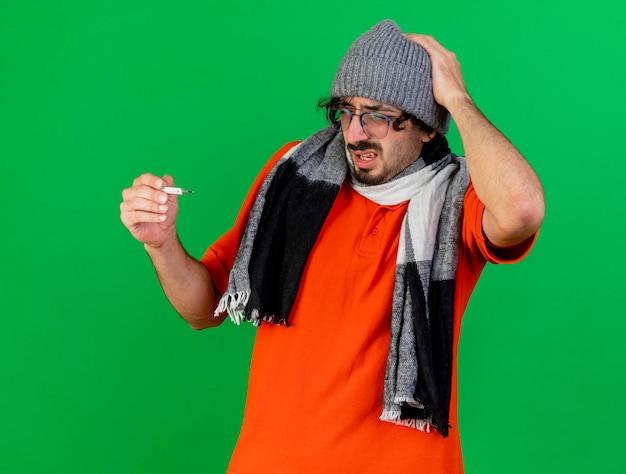 Bolący młody chory w okularach czapka zimowa i szalik trzymając i patrząc na termometr, trzymając rękę na głowie na białym tle na zielonej ścianie