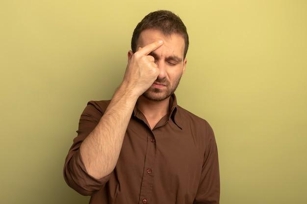 Bolący młody człowiek kaukaski wskazujący palec na czole z zamkniętymi oczami mający ból głowy na białym tle na oliwkowym tle z miejsca na kopię