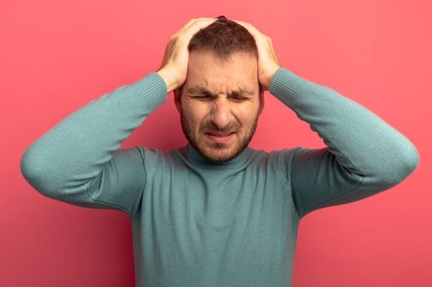 Bolący młody człowiek kładzie ręce na głowie cierpiącej na bóle głowy z zamkniętymi oczami na białym tle na różowej ścianie