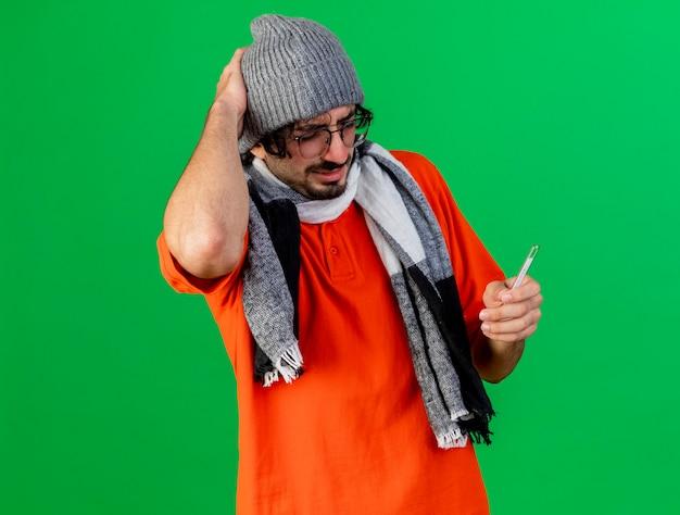 Bolący młody kaukaski chory człowiek w okularach czapka zimowa i szalik trzyma termometr trzymając rękę na głowie na białym tle na zielonym tle z miejsca na kopię