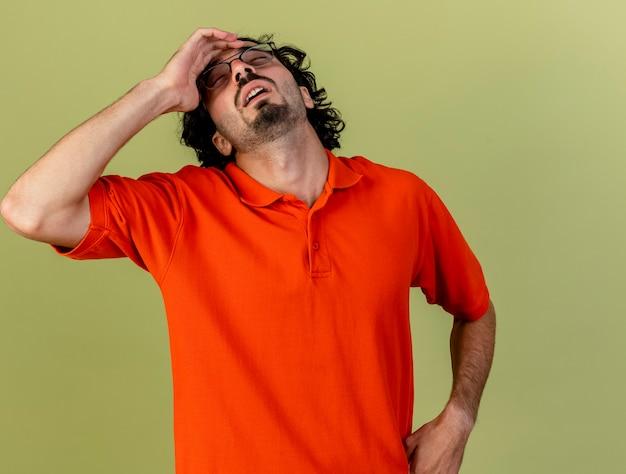Bolący młody kaukaski chory człowiek w okularach dotykając głowy z zamkniętymi oczami na białym tle oliwkowej zieleni z miejsca na kopię