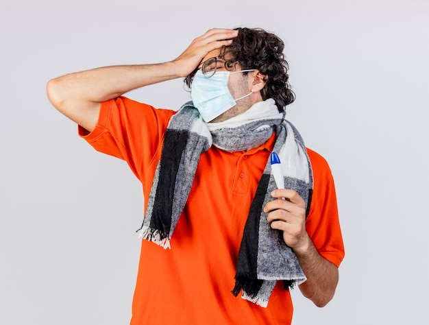 Bolący młody kaukaski chory człowiek w okularach maska i szalik trzyma termometr kładąc rękę na głowie z zamkniętymi oczami na białym tle na białej ścianie
