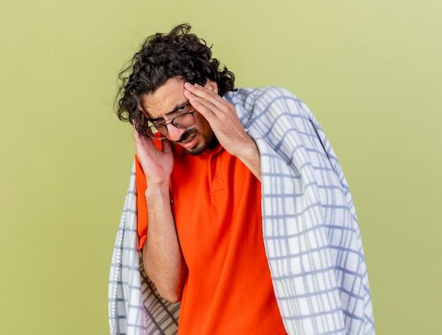Bolący młody kaukaski chory człowiek w okularach zawinięty w kratę, dotykając głowy mając ból głowy na białym tle na oliwkowej ścianie z miejsca na kopię