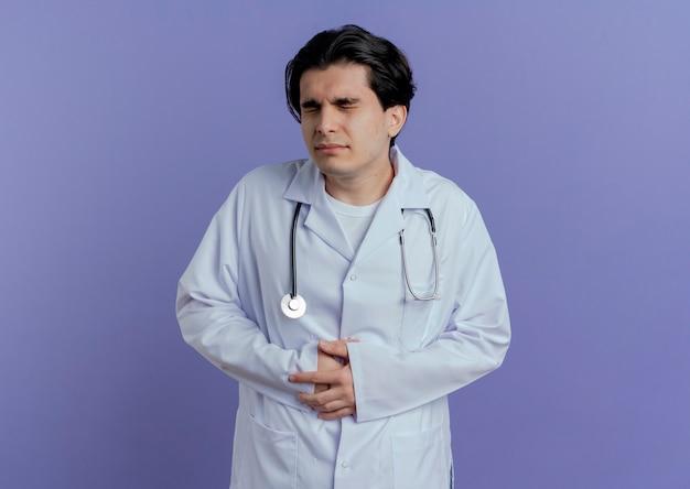 Bolący młody mężczyzna lekarz ubrany w medyczny szlafrok i stetoskop trzymając brzuch z zamkniętymi oczami na białym tle na fioletowej ścianie z miejsca na kopię